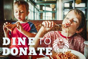 Image of boys eating at a restaurant linked to Dine to Donate page.